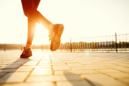 woman fitness: Pieds runner running on closeup route sur la chaussure. femme de remise en forme le lever du soleil jogging notion welness s�ance d'entra�nement. Banque d'images