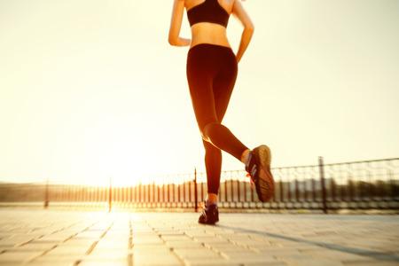 athletes: Pieds runner running on closeup route sur la chaussure. femme de remise en forme le lever du soleil jogging notion welness s�ance d'entra�nement. Banque d'images