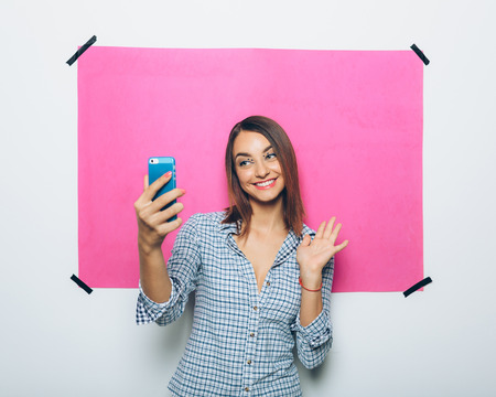 taking video: Pretty young woman taking picture with camera phone over pink background