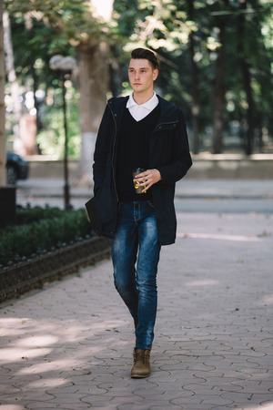 brief case: Stylish hipster model walking and holding coffee and brief case Stock Photo