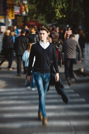 atractive: Young man cross the street at a crosswalk