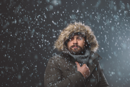 Handsome bearded man in snow storm