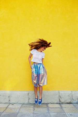 attractive girl: Attractive girl in an unusual skirt posing near a yellow wall Stock Photo