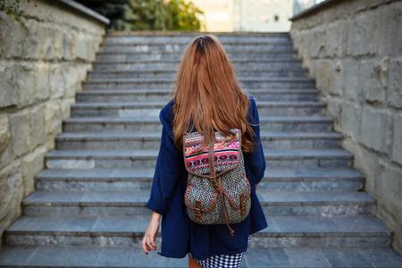 mochila viaje: Muchacha del estudiante con una mochila para subir escaleras. Vista trasera