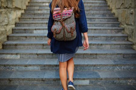 階段を登るバックパックを持つ学生少女。背面図