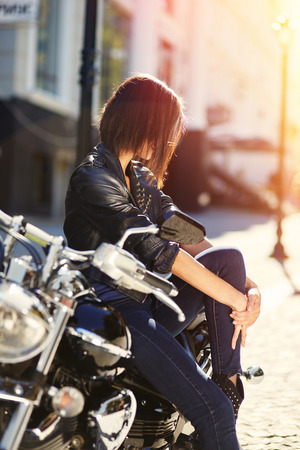 Biker girl in a leather jacket sitting on motorcycle with light leaks effect