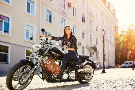 Biker girl in a leather jacket riding a motorcycle with ligth leak and motion effect Stock Photo