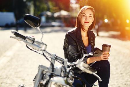 motorrad frau: Radfahrerm�dchen in einer Lederjacke auf einem Motorrad trinken Kaffee mit Licht Leck-Effekt