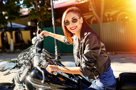 Biker girl in a leather jacket riding a motorcycle with ligth leak and motion effect Standard-Bild
