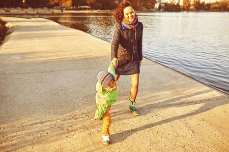 Mom and son having fun by the lake. Warm filter and film effect Stock Photo