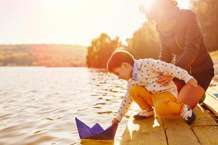 Moeder en zoon spelen met document boten op het meer. Warm filter en film effect Stockfoto