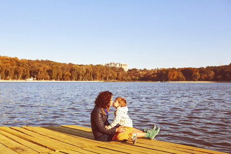 Mom and son resting by the lake. Warm filter and film effect