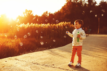 Little boy playing with soap bubbles. Warm filter and film effect