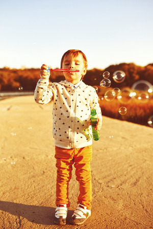 Little boy playing with soap bubbles. Warm filter and film effect photo