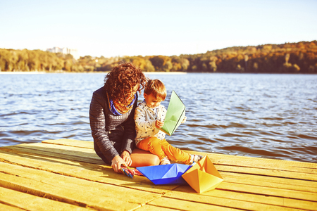 Mom and son playing with paper boats by the lake. Warm filter and film effect