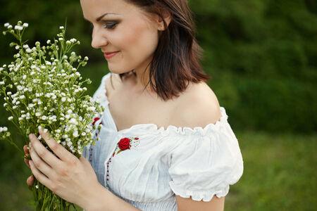 femme romantique: Portrait de la beaut� femme romantique tenant bouquet de fleurs sauvages Banque d'images