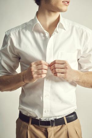 unbutton: Handsome young man unbutton his shirt, close up Stock Photo