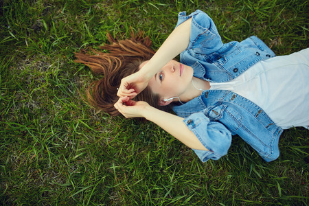 Relaxed woman listening to the music with headphones lying on the grass of a garden photo