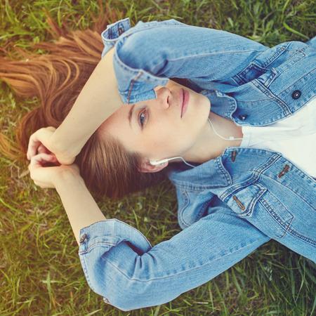 jeune fille: Femme d�tendue �couter de la musique avec un casque couch� sur l'herbe d'un jardin