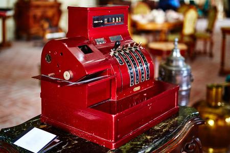 Red old-time cash register in a shop Foto de archivo