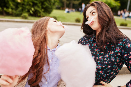 lifestyle caucasian: Two cheerful sisters eating cotton candy at the park