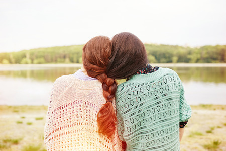 Two sisters with interwoven hairs looking at the lake. Light leak effect