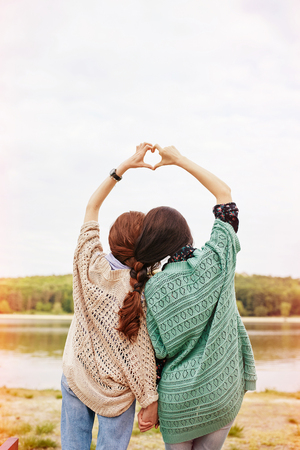 two sisters with interwoven hairs making heart above their heads at the lake