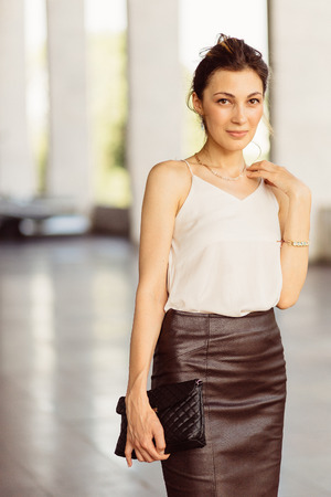 Portrait of a business woman in leather skirt with Stock Photo