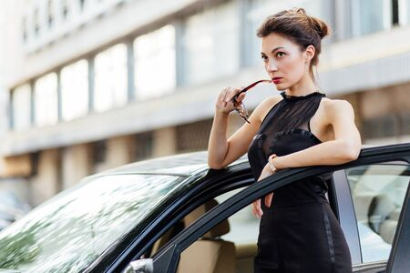 Attractive girl standing near the car in the city Stock Photo