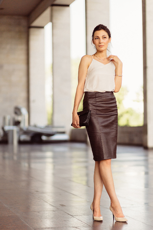 leather skirt: Portrait of a business woman in leather skirt with Stock Photo