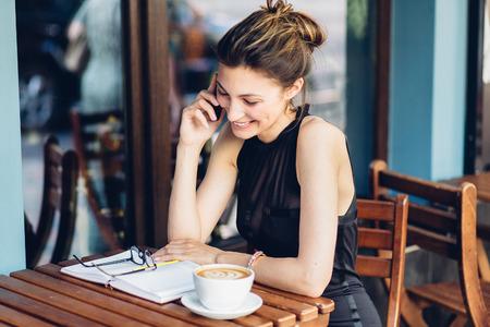 personas sentadas: Atractiva chica hablando por tel�fono en el caf�