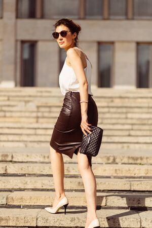bajando escaleras: Mujer de negocios con gafas de sol caminando en las escaleras