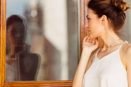 Attractive femme regardant son reflet dans la fenêtre
