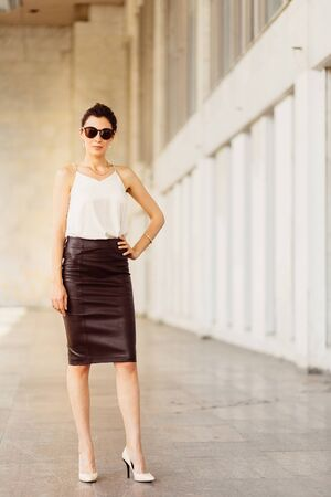 leather skirt: Portrait of business woman in sunglasses and leather skirt