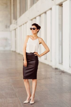 Portrait of business woman in sunglasses and leather skirt