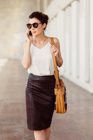 Business woman with mobile phone and bag on his shoulder