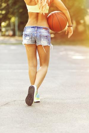 baloncesto chica: Chica sexy posando y jugando con una pelota de baloncesto. Efecto de pel�cula de la c�mara