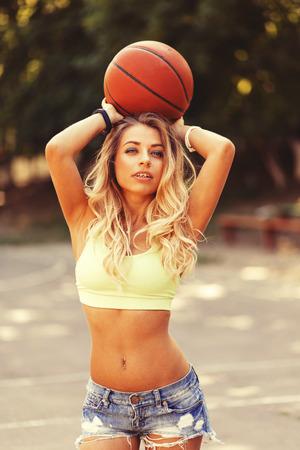 baloncesto chica: Chica sexy posando y jugando con una pelota de baloncesto. Efecto de película de la cámara