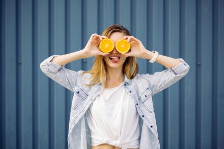 ni�as sonriendo: Mujer sonriente que sostiene dos pomelos en las manos sobre un fondo azul