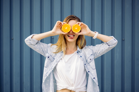 cute girl: Smiling woman holding two grapefruits in hands on a blue background Stock Photo