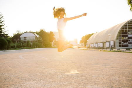 Outdoor summer lifestyle image of young pretty hipster woman having fun, listening music and dancing