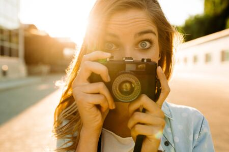 Hipster woman taking photos with retro film camera