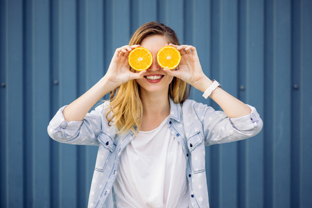 human hand: Smiling woman holding two grapefruits in hands on a blue background Stock Photo