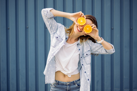 Smiling woman holding two grapefruits in hands on a blue background 스톡 콘텐츠