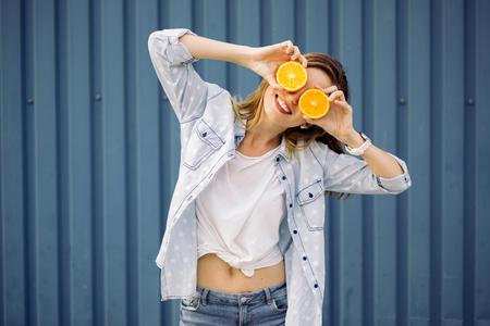 aliments droles: Sourire femme tenant deux pamplemousses dans les mains sur un fond bleu Banque d'images