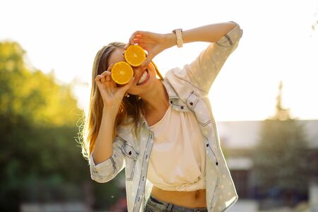 Portrait of smiling woman holding two grapefruits in hands Standard-Bild