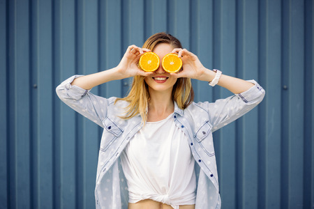 woman eating fruit: Smiling woman holding two grapefruits in hands on a blue background Stock Photo