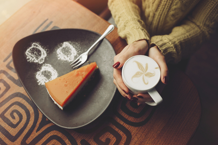 cappaccino: charming girl drinking cappuccino and eating cheesecake in coffee shop. Hands close up Stock Photo