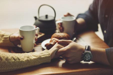 コーヒーを飲むことを愛するでカップル、コーヒー ショップで楽しい時を過します。概念が大好きです。ビンテージ効果のスタイルの写真。手をク