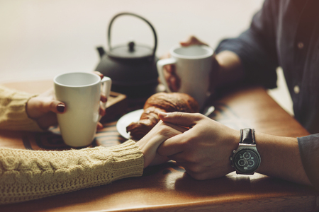 Couple in love drinking coffee and have fun in coffee shop. Love concepts. Vintage effect style picture. Hands close up